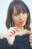 College girl. An intellectual ?. An image of an attractive girl deep in thought and with a pencil in her mouth. The position of the spectacles also indicates an Royalty Free Stock Images