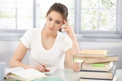 College girl learning at home thinking. College girl sitting at desk, learning at home, thinking Royalty Free Stock Photo