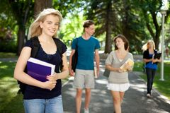 College Girl Portrait. Pretty blond college girl looking at camera with friends in background Stock Images