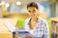College girl reading book. Happy college girl reading a book in library Royalty Free Stock Photo