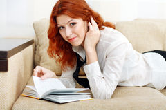 College girl relaxing on sofa with book Royalty Free Stock Images
