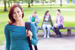 College girl smiling with blurred students in park Stock Image