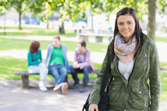 College girl smiling with blurred students in park Stock Photos
