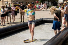 College girl surf rides in the city center. SZCZECIN, POLAND - MAY 23, 2014: Juwenalia, is an annual students' holiday in Poland, usually celebrated for three Stock Photos