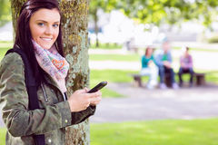 College girl text messaging with blurred students in park Royalty Free Stock Photography