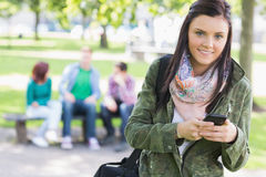 College girl text messaging with blurred students in park Royalty Free Stock Images