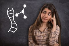 College girl thinking with DNA molecule. Portrait of a beautiful young woman or college girl thinking front of blackboard with DNA molecule royalty free stock photo