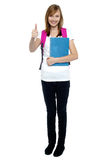 College going blonde showing thumbs up sign. Smart young college going blonde in trendy clothes showing thumbs up sign Royalty Free Stock Photos