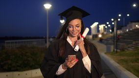 College graduate girl walking with diploma smiling and using her smartphone. stock video