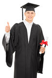 College graduate giving a thumb up. Proud young college graduate in a graduation gown holding a diploma and giving a thumb up isolated on white background Stock Images
