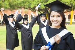 College graduate with happy classmates Stock Photos
