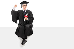 College graduate holding a diploma seated on panel Stock Photo