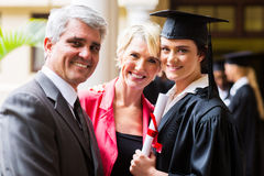College graduate with parents. Beautiful female college graduate with parents on graduation day Stock Images