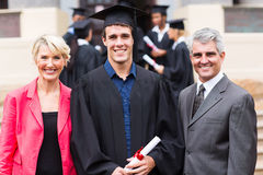 College graduate parents. Cheerful male college graduate and parents at graduation ceremony Stock Image