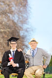 College graduate posing with his father in park Stock Image