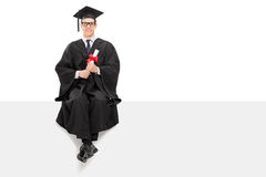 College graduate sitting on a blank billboard Royalty Free Stock Image