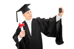 College graduate taking a selfie with phone Stock Image