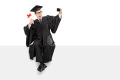 College graduate taking selfie seated on a panel Stock Image