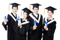 College graduates in graduation gowns standing  and smiling. Asian college graduates in graduation gowns standing  and smiling Royalty Free Stock Photography