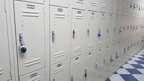 College / high school student badge lockers. School lockers off white, black and white tile floor royalty free stock image
