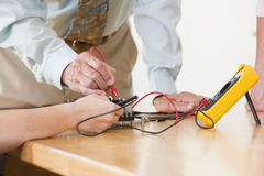 College instructor demonstrating use of multimeter. Engineering professor assisting student with proper use of probes and multimeter measurement on circuit board royalty free stock photography