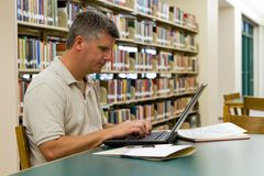 College Library Laptop. Middle-aged college student types on a laptop in the library Stock Images