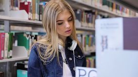 College Library. Student Girl Looking Books On Bookshelves