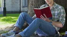 College male student sitting under tree, reading book for self-development. Stock footage stock footage