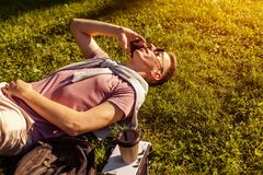 College man chilling in spring campus park. Happy guy student lying on grass talking on phone with book and coffee. Handsome college man chilling in spring Stock Photography