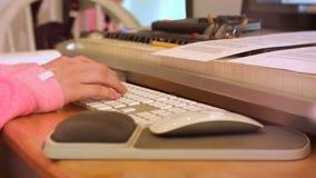 College-Oberschülerin-Arten auf Computer-Tastatur hinter Stapel Büchern stock footage