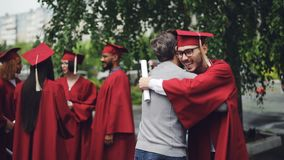 College professor is congratulating his student after graduation ceremony hugging him and shaking hand, teacher is proud