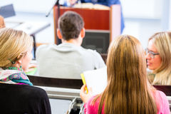 College professor giving lecture for students. Standing at desk Royalty Free Stock Photos