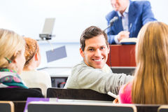 College professor giving lecture for students. Standing at desk Royalty Free Stock Photo