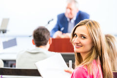 College professor giving lecture for students. Standing at desk Royalty Free Stock Photography