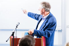 College professor giving lecture for students. Standing at desk Stock Images