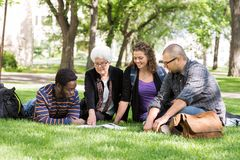 College Professor Helping Students. College professor assisting group of senior students Royalty Free Stock Images