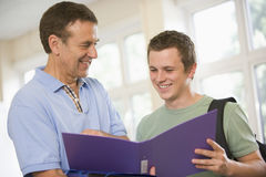 College professor providing guidance to a student. College professor providing guidance to a male student stock photography