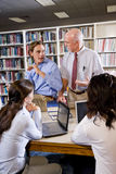 College professor with students talking in library