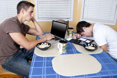 College Roommates eating breakfast. 2 college room mates eat breakfast at the kitchen table after a late night of studying stock photos
