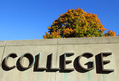 College sign with colorful tree. Metal letters on stone sign for an institution of higher learning (college or university) with blue sky background and fall Royalty Free Stock Photography