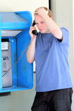 College stress on a Pay Phone. A typical american college teenager, stressed, calling on a pay phone. Short hair, shallow depth of field, selective focus. Copy Royalty Free Stock Image
