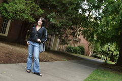 College student. Female college student with a college campus in the back ground Royalty Free Stock Image