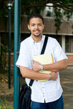 College student. Portrait of a young male african college student standing outside of classroom with a should bag and books outdoors Royalty Free Stock Photo