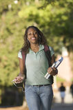College Student. Girl in college between classes carrying books and listening to iPod royalty free stock photos