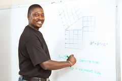 College Student - Advanced Math. Handsome African-American college student (or teacher) doing trigonometry equations on the white board stock photography