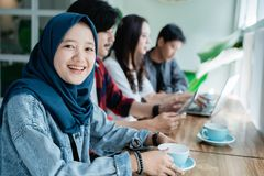 College student asian with friend in cafe. Asian veiled college student with friend working together in cafe royalty free stock photos