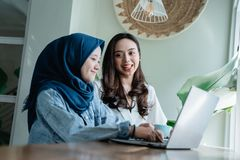 College student asian with friend in cafe. College student asian with friend working together in cafe royalty free stock photo