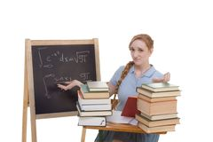 College student by blackboard studying math exam. High school or college Caucasian redhead woman student sitting by the desk. Blank blackboard with advanced Stock Photography