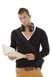 College student with book handheld. Stylish and goodlooking college student guy with book handheld, looking at camera, frowning Stock Photos