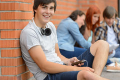 College student boy sitting ground with friends Royalty Free Stock Image